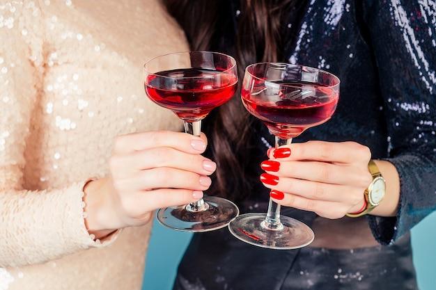 Les mains de deux femmes en robe de soirée cocktail à paillettes brillantes tiennent un verre de vin lors d'une fête sur fond bleu studio.