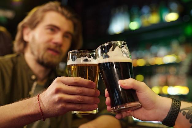 Mains de deux gars sympathiques trinquant avec des verres de bière devant la caméra tandis que l'un d'eux prononce un toast contre un bar avec des boissons alcoolisées