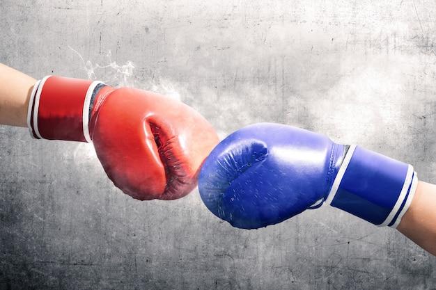 Les mains de deux hommes avec des gants de boxe bleus et rouges se sont cogné les poings