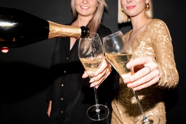 Mains de deux jeunes femmes élégantes tenant des flûtes pour le champagne pendant que quelqu'un verse la boisson de la bouteille à la fête dans la discothèque