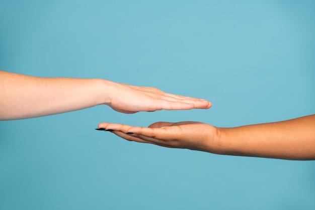 Mains de deux jeunes femmes d'ethnies caucasiennes et africaines à la peau blanche et foncée l'une en face de l'autre sur fond bleu