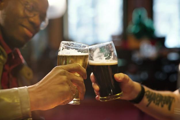 Mains de deux jeunes hommes interculturels tintant avec des verres de bière devant la caméra tout en passant du temps dans un pub moderne le jour de la saint patrick