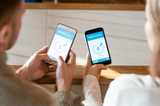 Mains de deux jeunes rendez-vous avec des smartphones lors de l'opération financière d'envoi et de réception d'argent via les services bancaires en ligne