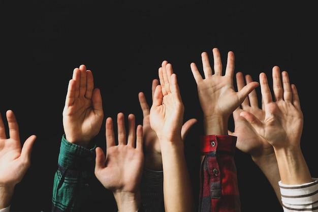 Les mains de différentes personnes se sont levées