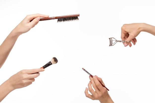 Mains avec différents produits de maquillage sur l'espace blanc