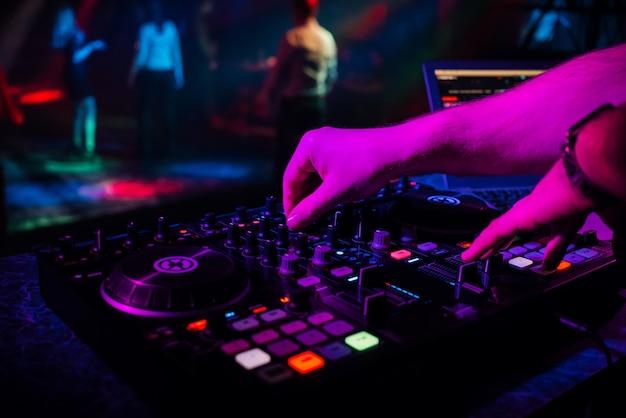 Mains dj mixant et jouant de la musique sur une console de mixage professionnelle