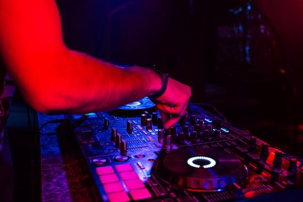 Mains d'un dj mixant de la musique sur un contrôleur professionnel dans une cabine
