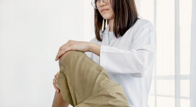 Mains de docteur féminin faisant la thérapie physique en étendant la jambe et le genou d'un patient masculin.