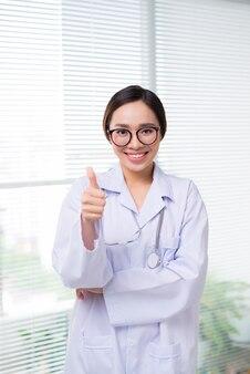 Mains de docteur féminin avec le geste de pouce vers le haut