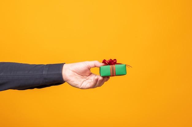 Mains donnant une boîte-cadeau sur fond jaune