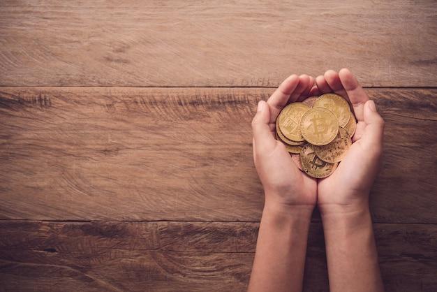 Mains donnant une pièce d'or sur un plancher en bois - aide concept pour les entreprises