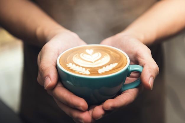 Mains donnant une tasse de café d'art latte