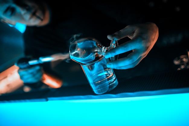 Les mains du barman, gobelet en verre sur le comptoir