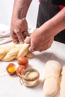 Les mains du boulanger tissent de la pâte à pain. nourriture authentique israélienne pain de challah cru