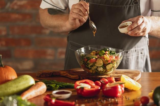 Les mains du chef coupant des légumes dans sa cuisine