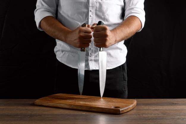 Mains du chef avec des couteaux