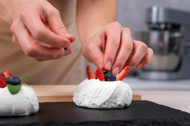 Les mains du chef pâtissier décore le gâteau avec des fraises fraîches et des myrtilles