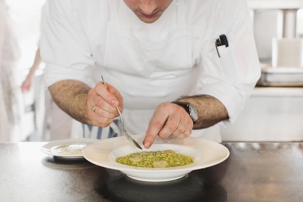 Mains du chef préparant un délicieux risotto