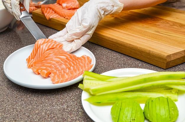 Les mains du chef se bouchent. sur une planche à découper en bois, le chef découpe un poisson rouge au couteau. saumon pour sushi japonais
