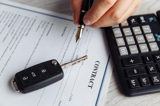 Mains du client signant le formulaire de location de voiture