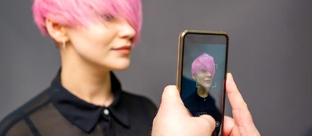 Les mains du coiffeur homme prenant la photo sur le smartphone de sa coiffure rose courte de client.