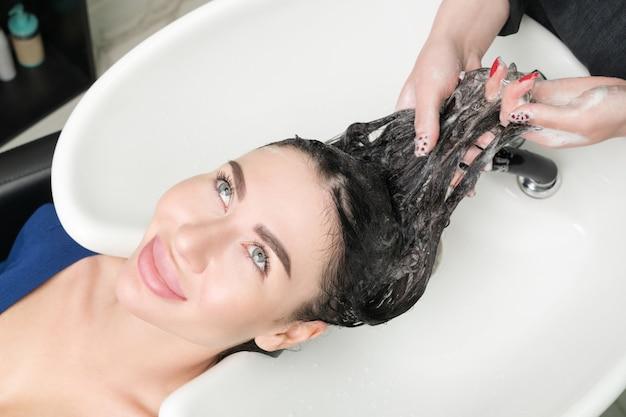 Les mains du coiffeur professionnel lavent les cheveux longs d'une femme brune avec un shampooing dans un évier professionnel pour un shampooing dans un salon de beauté.