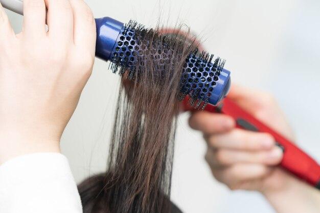 Les mains du coiffeur sèchent les cheveux bruns du client à l'aide d'une brosse à cheveux bleue et d'un sèche-cheveux rouge dans un salon de beauté professionnel.