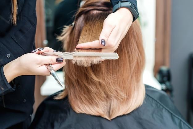 Les mains du coiffeur tiennent les cheveux rouges dans le salon de beauté.