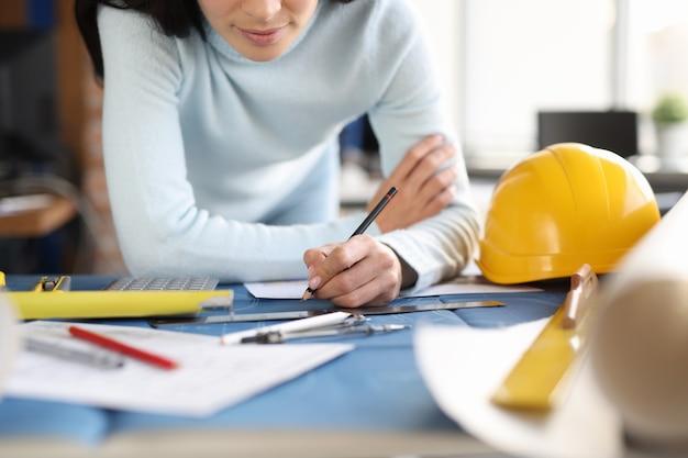Les mains du constructeur de concepteur dessinent un dessin sur le développement de la table dans le domaine du concept de construction