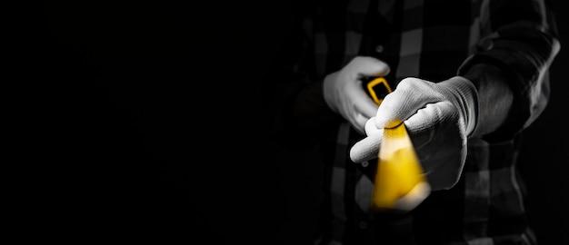 Les mains du constructeur dans des gants blancs tenant un mètre ruban rétractable jaune et le montrant devant la caméra, en gros plan. bannière avec espace de copie pour le texte.