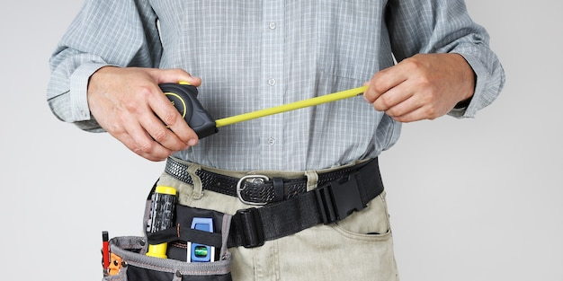 Les mains du constructeur tiennent l'étalon pour mesurer pendant le travail et les outils dans le sac banane