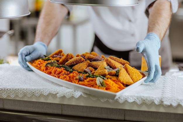 Les mains du cuisinier masculin dans des gants médicaux bleus mettant sur un grand plat