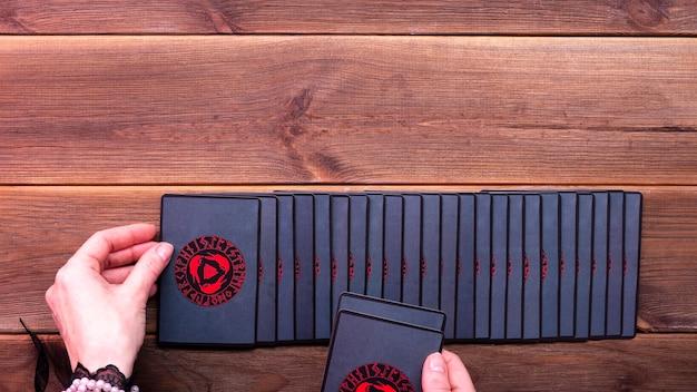 Les mains du diseur de bonne aventure et les cartes de divination sur une table en bois. concept de divination, cartes de tarot, médium.