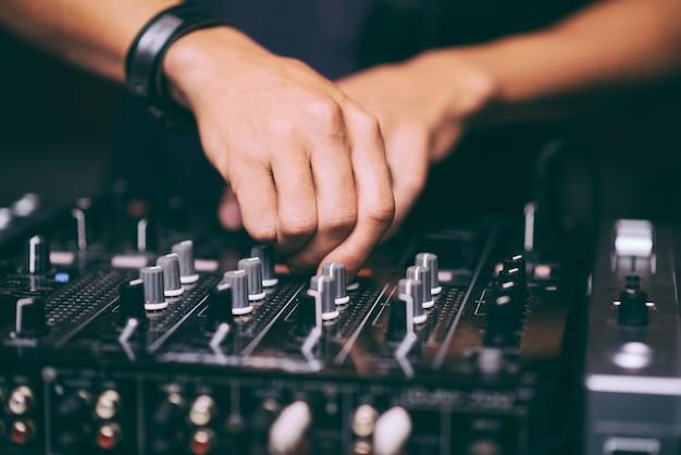 Les mains du dj contrôlent le gros plan de la télécommande