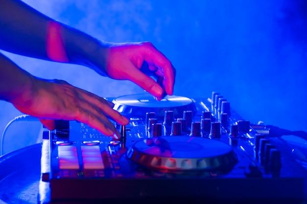 Les mains du dj sur scène mixent, disc jockey et mixent des pistes sur le contrôleur de mixage sonore, jouant de la musique au bar, disco tech ou soirée club.