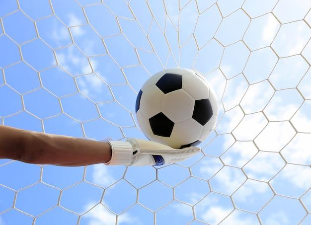 Les mains du gardien de but de football atteignant pour la balle, avec filet et le ciel en arrière-plan