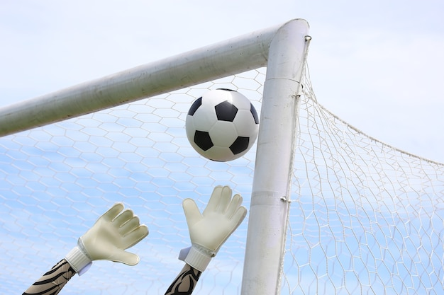 Les mains du gardien de but de soccer atteignant pour la balle