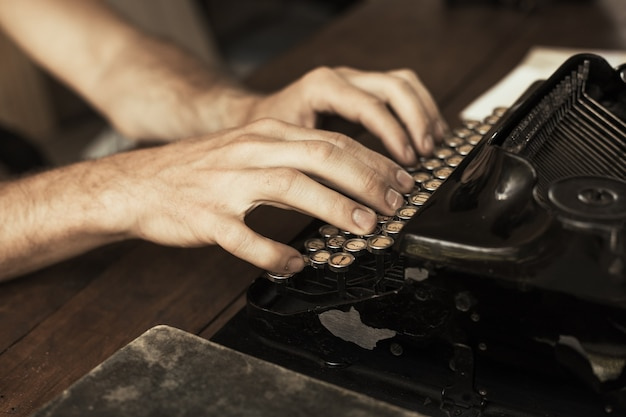 Les mains du jeune homme tapant sur une machine à écrire vintage antique