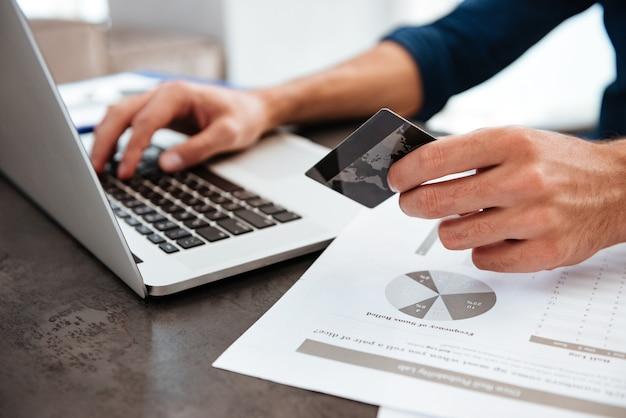 Les mains du jeune homme tenant une carte de crédit et la saisie. achats en ligne sur internet à l'aide d'un ordinateur portable.