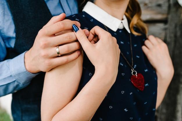 Les mains du mari embrassent une femme à l'arrière dans le contexte d'un mur en bois de la maison