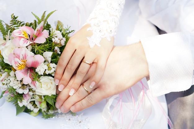 Les mains du marié et de la mariée avec des anneaux agrandi sans visage