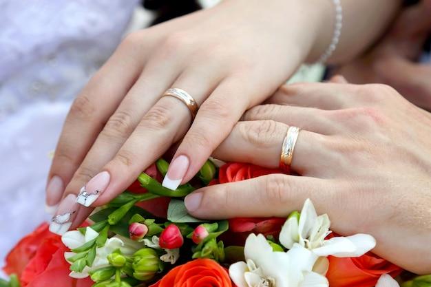 Mains du marié et de la mariée sur fond de bouquet de mariage. relations amoureuses et familiales