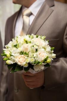 Les mains du marié se préparent en costume. le marié tient le bouquet de mariage.