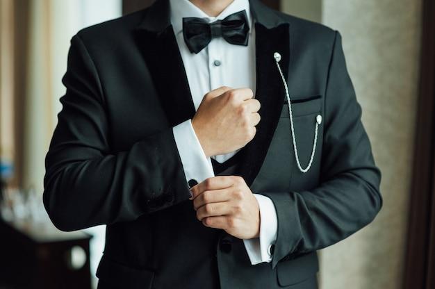 Les mains du marié se préparent en costume