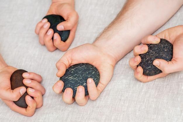 Les mains du masseur tenant des pierres de massage.
