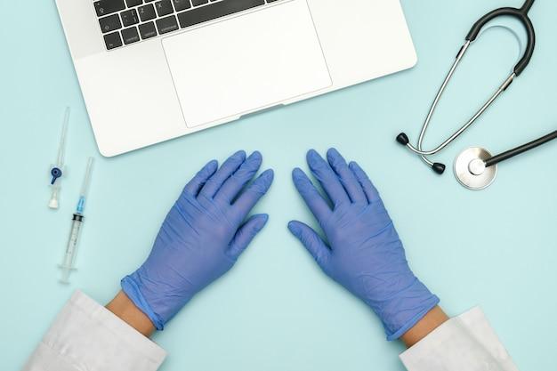 Mains du médecin sur le bureau bleu