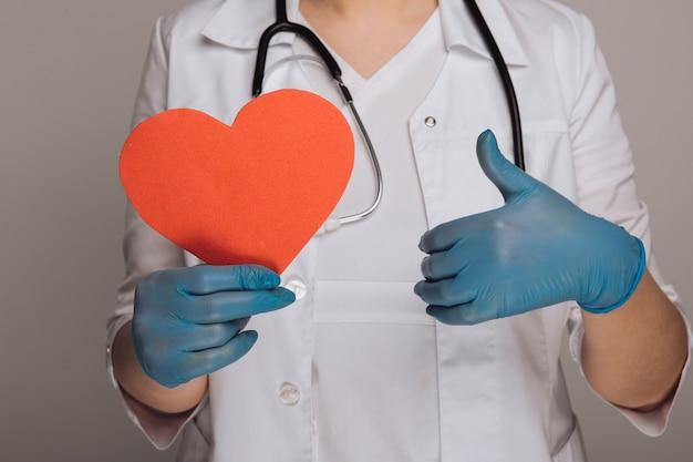 Les mains du médecin dans les gants tenant l'image du cœur. stéthoscope autour du cou.