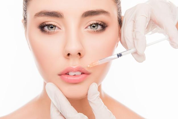 Mains du médecin faisant une injection dans les lèvres de la femme