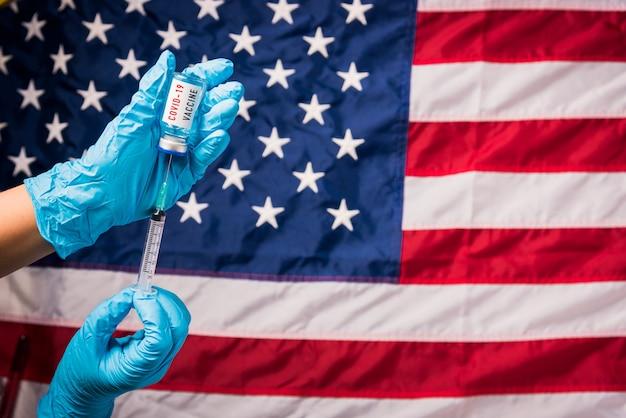 Les mains du médecin portent des gants tenant le vaccin contre le coronavirus covid et la seringue sur le drapeau des états-unis