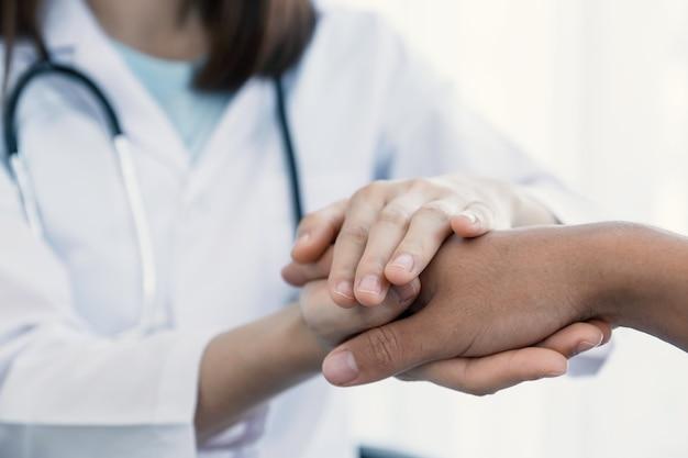 Les mains du médecin tenant la main du patient pour l'encourager et ont expliqué les résultats de l'examen de santé.